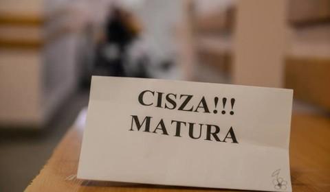 """kartka z napisem """"CISZA!!! MATURA"""" na szkolnej ławce"""